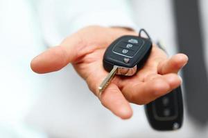 bilnycklar. säljaren hand ger nycklar