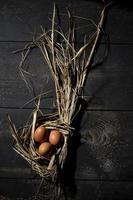 påsk rede, ägg i halm foto