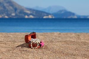 dekorativ bröst med smycken och sjöstjärnor på en strand foto