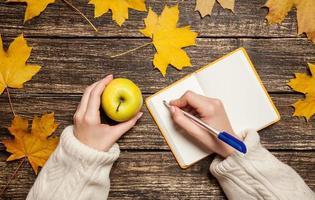 kvinnlig hand skriver något i anteckningsboken och håller äpplet foto