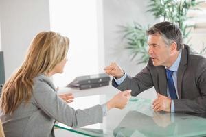 två arga medarbetare som argumenterar på ett kontor foto