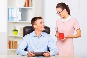 kollegan tar med sig en kopp drink till sin partner foto