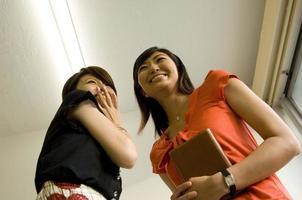 två unga japanska kvinnor som pratar i korridoren foto