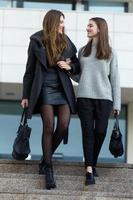 två unga affärskvinnor som går på gatan nära kontorsbyggnad foto