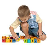 koncentrerad liten pojke med block på golvet foto