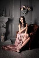 kvinna sitter i fåtölj i lång beige klänning. lyx