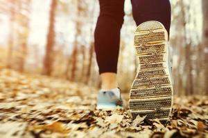 kvinna som joggar i skogen vid solnedgången