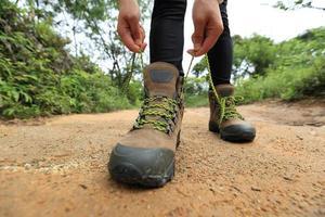 kvinna vandrar knyta skosnören på skogsstig