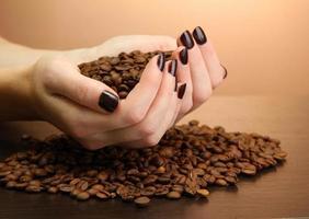 kvinnliga händer med kaffebönor, på brun bakgrund foto