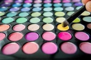 palett med färgglada ögonskuggor och sminkborste