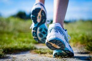 närbild på fötter löparskor i aktion på landsbygden foto