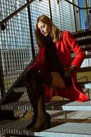 vacker flicka poserar med röd kappa foto