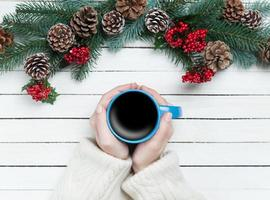 flicka håller kopp kaffe nära tallgrenar foto