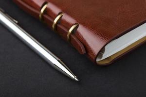 anteckningsbok och penna i komposition i svart foto