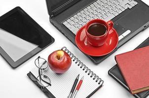 bärbar dator och kontorsmaterial på vit