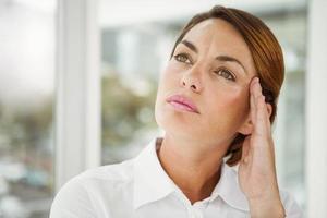 tankeväckande affärskvinna som tittar bort på kontoret foto