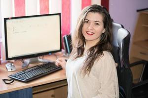 flicka som ler på sitt kontor foto