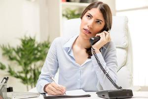 affärskvinna ringer på kontoret foto