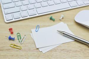 papper anteckningar, penna, klipp, mus och tangentbord på bordet foto