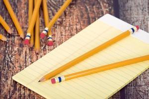 grupp gula pennor och en anteckningsblock foto