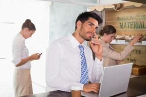affärsman som använder bärbar dator i kontorscafeteria foto