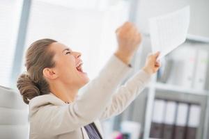 glad affärskvinna i office glädjer sig över framgång foto
