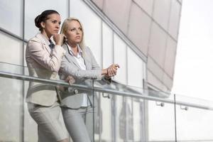 unga affärskvinnor på kontorsräcke som tittar bort foto