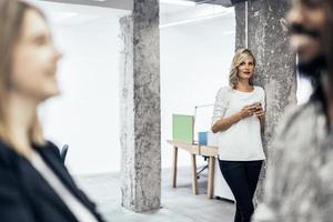 vacker blond kvinna på kontoret med hjälp av telefon foto