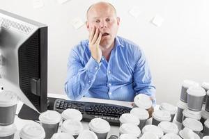 överarbetad och utmattad affärsman på kontoret foto