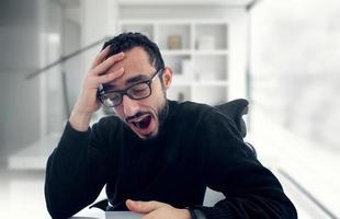 ung affärsman som gäspar på jobbet i office foto