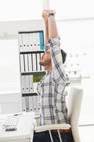 avslappnad affärsman som sträcker sig i svängbar stol foto