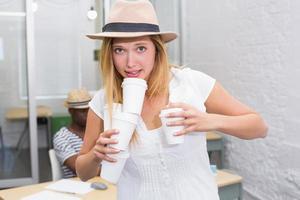 avslappnad kvinna som håller disponibel koppar i office foto