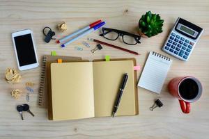 kontorstillförsel och kopp kaffe på skrivbordet, arbetsplatsen foto