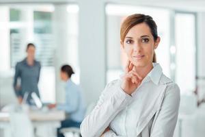 säker kvinna entreprenör poserar på sitt kontor foto