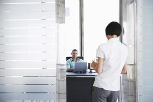 man pratar med kvinnan som står på kontorsdörröppningen foto