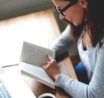 kvinna som läser en bok på hemmakontoret. foto