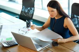 porträtt av en förvirrad affärskvinna som arbetar med papper foto