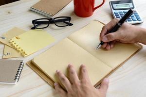 anteckningsbok med kopp kaffe och kontor på skrivbordet foto