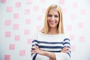 avslappnad tjej som står med armarna vikta på kontoret foto