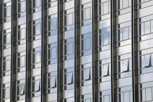 moln återspeglas i fönster i modern kontorsbyggnad foto