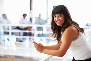 leende kvinna i office med smart telefon som ler mot kameran foto