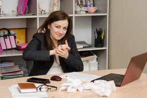 tjej på kontoret i händerna som skrynklar ett papper foto