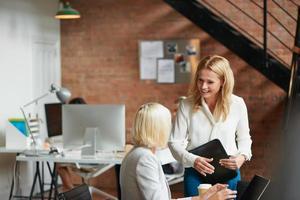 teamledare som erbjuder råd till praktikant i upptagen trendiga kontor foto