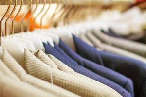 snygga jackor som hänger på racket i butiken foto