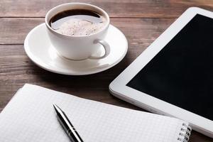 surfplatta, anteckningsbok och kaffe på bordet foto