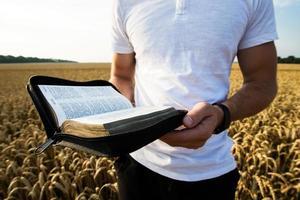 man som håller öppen bibel i ett vetefält foto