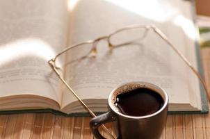 kopp kaffe, står bredvid en öppen bok foto