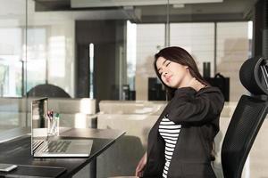 ung affärskvinna med nacksmärta sitter vid skrivbordet foto