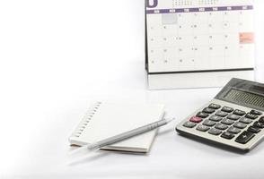 miniräknare och penna och anteckningsbok är nära kalender. foto