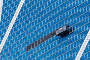 upphängda arbetsplattformar på blå byggnad foto